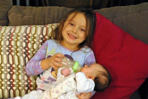 Big sister feeding infant success