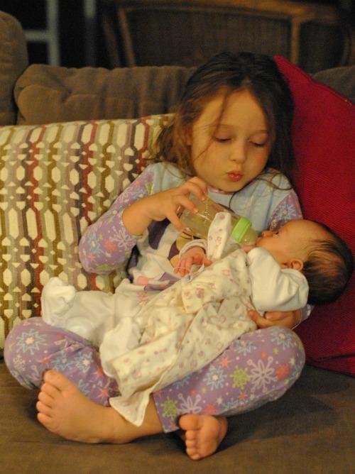 Big sister feeding infant