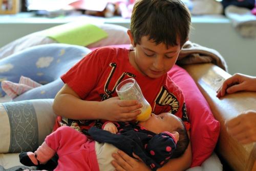 Big brother feeding baby