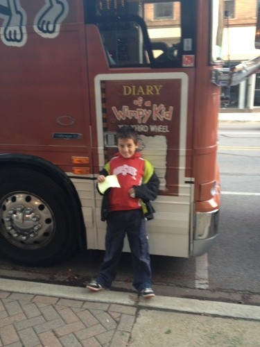 child in front of Diary of a Wimpy Kid Tour Bus