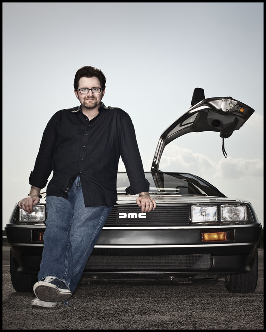 Ernest Cline sitting on hood of tricked out Delorian, vehicle Wade's avatar drives in the OASIS.